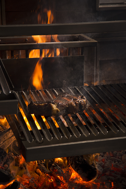 "A steak sizzles on the grill in the ""fire pit."""