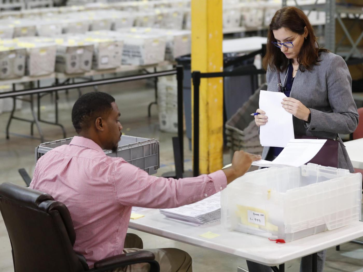 A Republican party observer, right, watches as an employee at the Palm Beach County Supervisor Of Elections office goes through a stack of damaged ballots, Thursday, Nov. 15, 2018, in West Palm Beach, Fla.