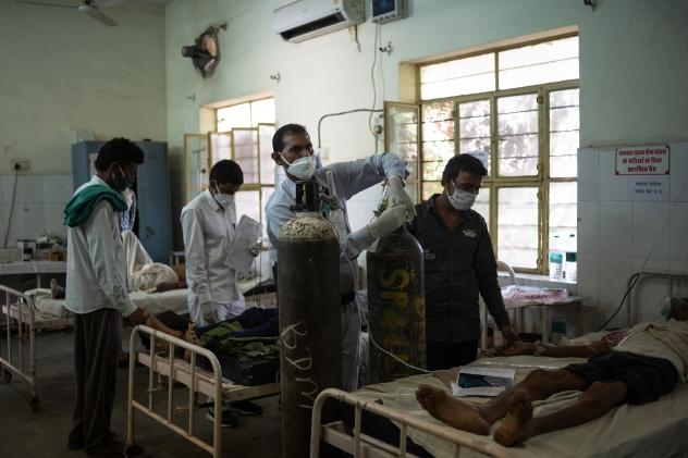 Medical attendant Gurmesh Kumawat prepares to administer supplemental oxygen to a coronavirus patient in the emergency ward at the BDM Government Hospital in mid-May in Kotputli, India.
