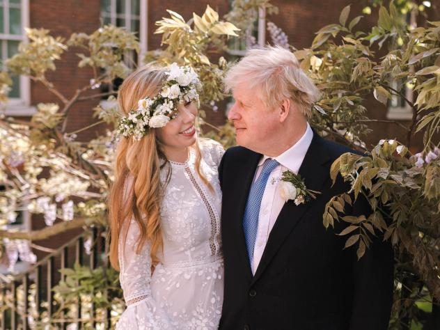 Prime Minister Boris Johnson poses with his wife Carrie Symonds in the garden of 10 Downing Street following their wedding at Westminster Cathedral on Saturday in London.