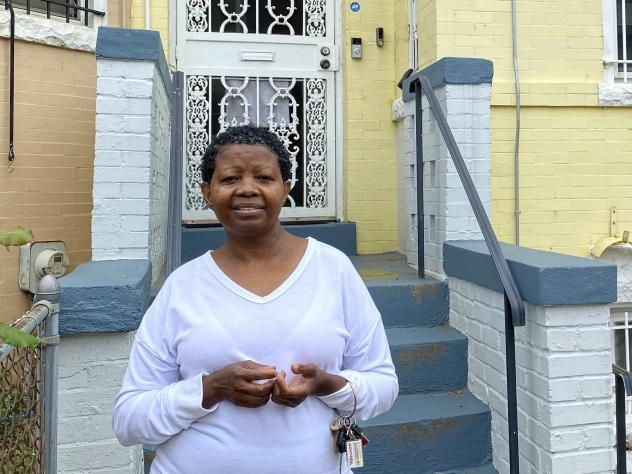 Katherine Gaines stands in front of her childhood home in Washington, D.C. She moved back in two years ago to help care for her mother, who has Alzheimer's disease.