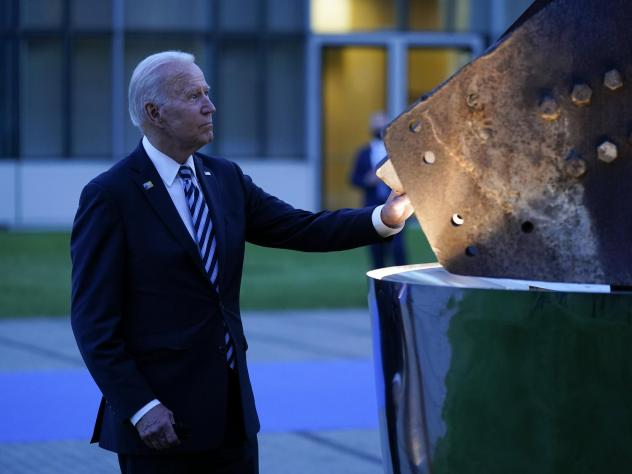 President Biden touches a piece of steel from the World Trade Center at a memorial to the 9/11 attacks Monday at NATO headquarters in Brussels. NATO allies joined in a collective defense with the U.S. after the terror attacks.