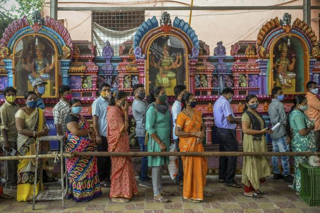 On June 25, people queued up to register for a COVID-19 vaccine at a site outside a Hindu temple in Hyderabad. Vaccinations are now being administered after a series of missteps led to a shortage of doses. If all goes well, India's public health agency h