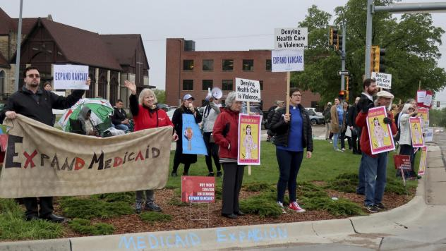 Advocates for expanding Medicaid in Kansas staged a protest outside the entrance to the statehouse parking garage in Topeka in May 2019. Today, twelve states have still not expanded Medicaid. The biggest are Texas, Florida, and Georgia, but there are a f