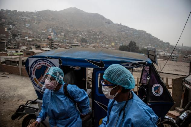 Health workers arrive in a tuk-tuk to administer doses of the Pfizer COVID-19 vaccine to elderly citizens in their homes in Lima, Peru, in April.