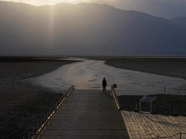 A person walks on a boardwalk at the salt flats at Badwater Basin on Aug. 17, 2020, in Death Valley National Park in California. Temperatures reached 130 degrees there on Friday.
