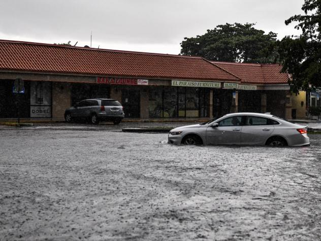 A woman drives through floodwater during heavy rainfall in Miami. A new study predicts that high tide flooding in coastal areas could increase in frequency because of climate change and the lunar cycle in the mid-2030s.