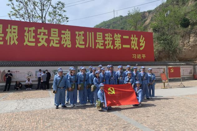 """Tourists dressed up as People's Liberation Army soldiers pose in Liangjiahe village, where a teenage Xi Jinping spent seven years doing hard labor. Today the village is a popular red tourism site. The sign displays a quote from Xi: """"Liangjiahe is where m"""