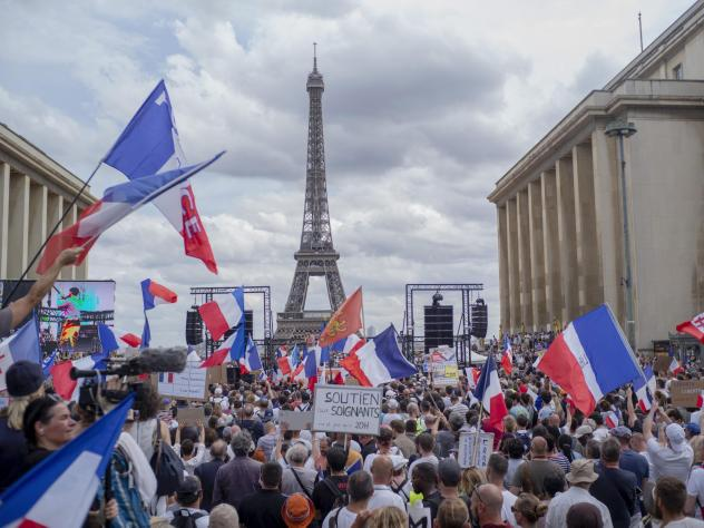 Thousands of protesters gather near the Eiffel Tower to protest the COVID-19 pass which grants vaccinated individuals greater ease of access to venues.