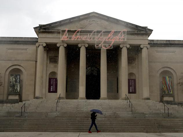 A man covers himself from rain with an umbrella as he walks by the Baltimore Museum of Art on April 21, 2020. An upcoming exhibit at the museum will be curated by security guards.