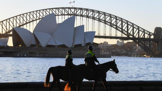 Mounted police officers patrol around the edge of Sydney Harbor on Friday as the Australian city has been locked down amid a new surge in coronavirus infections.