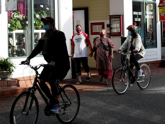 Pedestrians and cyclists head down Commercial Street in Provincetown, Mass., in May 2020. A study of a new outbreak in Provincetown found that three-quarters of those infected with the virus were fully vaccinated.