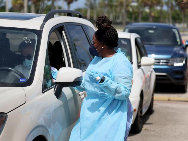 A health care worker at a drive-through site prepares to administer a COVID-19 vaccine on July 26 in Miami.