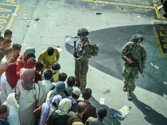 U.S. soldiers stand guard as Afghans wait Monday at the Kabul airport following the swift end to Afghanistan's 20-year war.