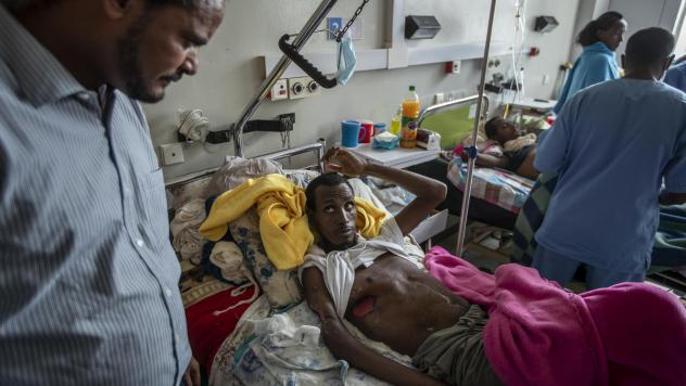 In a May 6, 2021 file photo, a farmer, Teklemariam Gebremichael, who said he was shot by Eritrean forces in Enticho six months before and is still recovering, speaks to a doctor, left, at the Ayder Referral Hospital in Mekele, in the Tigray region of nor
