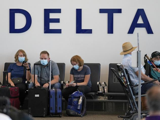 People sit under Delta sign at Salt Lake City International Airport on July 1, 2021. Delta Air Lines won't force employees to get vaccinated, but it's going to make unvaccinated workers pay a $200 monthly charge.