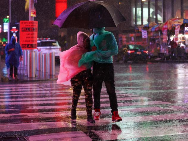 People out in the street during heavy rain and storm at Times Square in New York City on September 1, 2021.