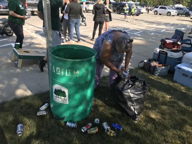 Holly Rutter collects cans from tailgaters on the campus of Michigan State University in East Lansing on Sept. 11, 2021. People in Michigan can get 10 cents for each can or bottle they return to a store.