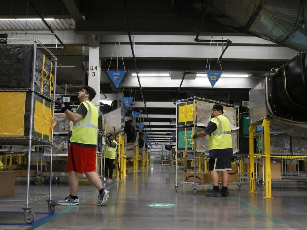 Amazon workers move containers to delivery trucks at an Amazon warehouse facility in Goodyear, Ariz., in December 2019.
