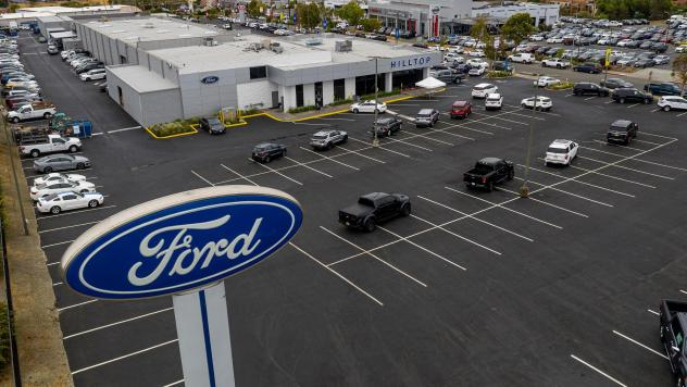 Vehicles sit in a nearly empty lot at a car dealership in Richmond, Calif., on July 1. The global semiconductor shortage has hobbled auto production worldwide, making it difficult to find a car to buy.