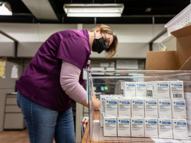 Janet Gerber, a health department worker in Louisville, Ky., processes boxes containing vials of the Johnson & Johnson COVID vaccine in March.