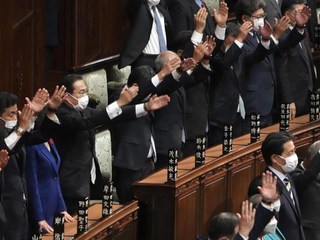 Japanese Prime Minister Fumio Kishida, forth from left, and other lawmakers give three cheers after dissolving the lower house, the more powerful of the two parliamentary chambers, during an extraordinary Diet session at the lower house of parliament Thu