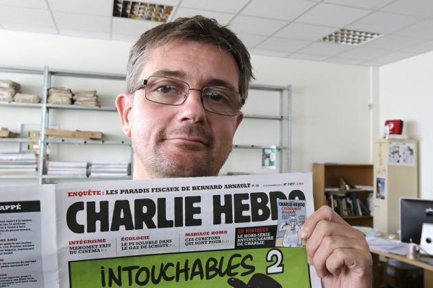 Stephane Charbonnier, the editor of <em>Charlie Hebdo, </em>poses with his magazine on Sept. 19, 2012. The magazine, which was attacked today, is part of a long tradition of French satire.