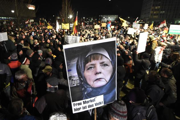 """A protester in Dresden, Germany, holds a poster Monday showing Chancellor Angela Merkel wearing a headscarf during a rally organized by PEGIDA, a group that is against what it calls the """"Islamization of Europe."""""""
