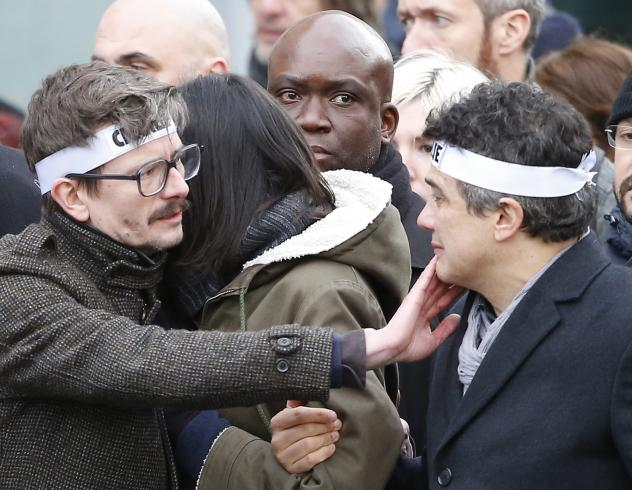 <em>Charlie Hebdo</em> editorialist Patrick Pelloux (right) and cartoonist Renald Luzier, known as Luz (left), join a march in Paris on Sunday.