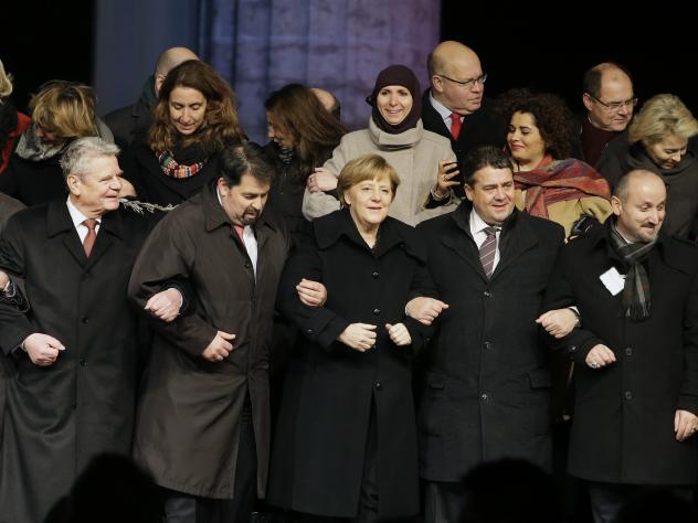 German Chancellor Angela Merkel, front third from left, attends a vigil in Berlin organized by a German Muslim group to commemorate the victims of last week's attacks in Paris.