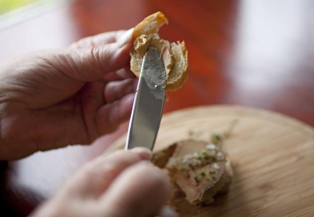 Karlene Bley of Los Angeles spreads her torchon of foie gras onto bread during lunch at the Presidio Social Club restaurant in San Francisco. Last week, a federal judge overturned California's ban on the dish.