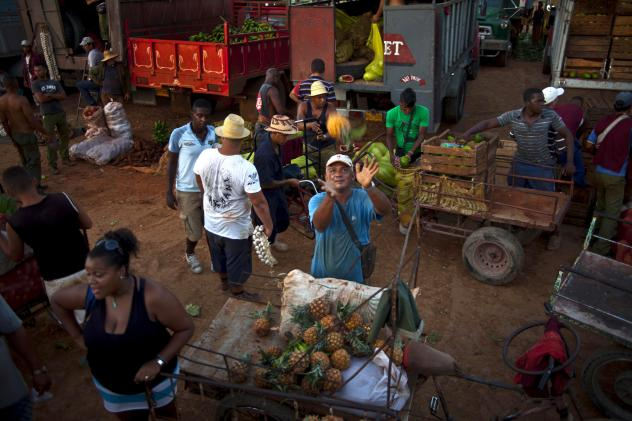 A vendor reaches out to catch a pineapple at a food market in the outskirts of Havana.