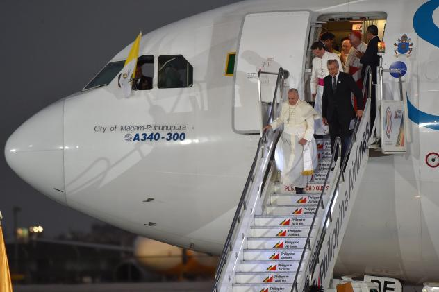 """Pope Francis disembarks from the plane upon his arrival at the airport in Manila, Philippines, on Wednesday. In comments to reporters aboard the plane, Francis said though the attack on <em>Charlie Hebdo</em> magazine was an """"aberration,"""" free speech """"ca"""