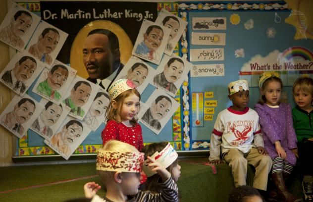 Semai Kebede shows off a photo of Dr. King he's keeping in his cubby. Barnhardt, who grew up in the segregated South, teaches her class about King's life and legacy, a history she's experienced firsthand.