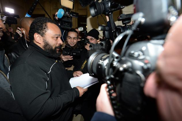 """French comedian Dieudonne M'Bala M'Bala arrives for his trial at the courthouse in Paris on Jan. 28. He goes on trial again today on charges of """"defending terrorism,"""" following remarks he made on Facebook after the deadly attack on the satirical weekly <"""