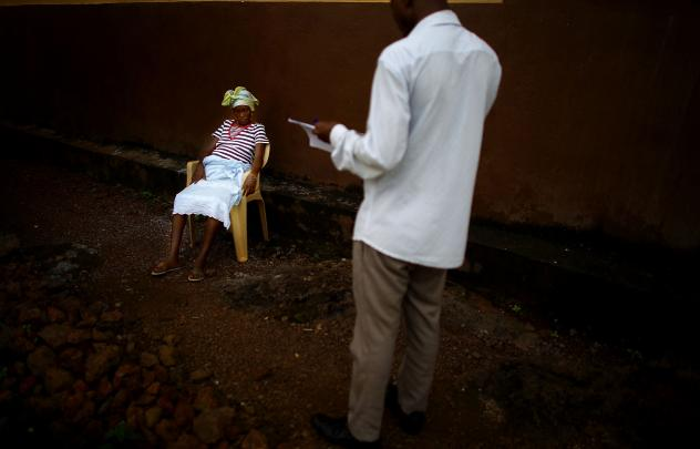 Survey teams are part of the Ebola army: They determine who's sick and send out burial teams when needed. Here, Osman Sow talks with Kadiatu, who is eight months pregnant and suspected of having the virus, as she waits at a health center in Freetown, Sie