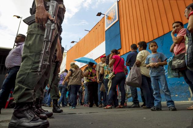 A man carries newly bought disposable diapers past a line of people waiting to enter a private supermarket to buy the same item in Caracas, Venezuela, on Jan. 16. The country's economy is in crisis, with high inflation, sinking oil revenues and shortages