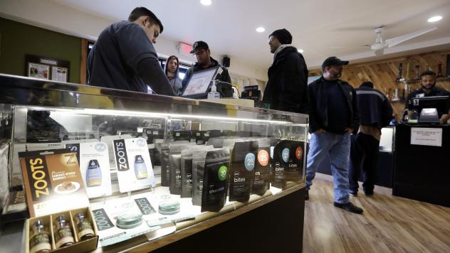 Customers browse the pot products at Cannabis City in Seattle. In Washington, the 2012 initiative to legalize pot was sold as a way to decrease expenses for local governments.