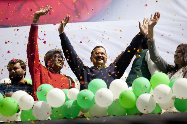 Aam Aadmi Party leader Arvind Kejriwal, center, waves to the crowd as his party secured a landslide victory in New Delhi, India, on Tuesday. The result is a huge blow for Prime Minister Narendra Modi's Bharatiya Janata Party.