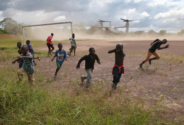 Boys run from blowing dust as a U.S. Marine vehicle takes off from an Ebola treatment center under construction in Liberia in October. In the end, the centers weren't always needed, but the military's ability to ferry supplies was critical in fighting th