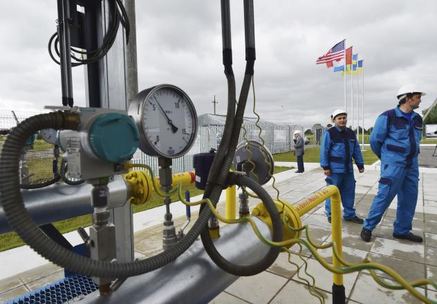 Workers stand next to a gas pipeline not far from the central Ukrainian city of Poltava in June 2014. Ukraine imports much of its gas from Russia, which is once again threatening to cut off supplies in a dispute over payments.