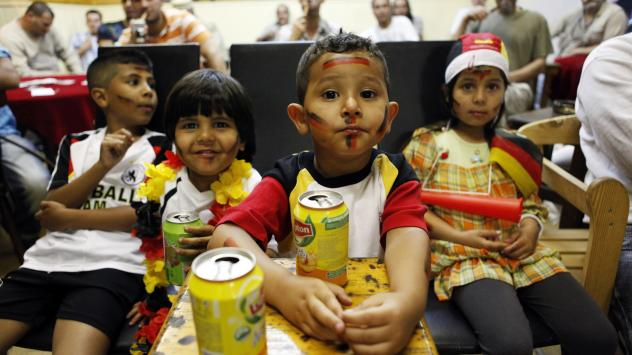 Young fans of the German national soccer team drink iced tea in July 2010 as they watch the FIFA World Cup semi-final match Germany vs. Spain in an Arabic cafe in Berlin's Neukölln district. The neighborhood has gentrified rapidly in recent years, but m
