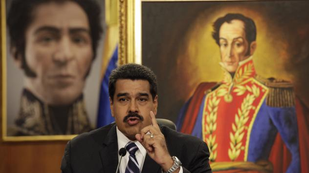 Between two portraits of Venezuela's hero Simon Bolivar in the background, President Nicolas Maduro speaks at a news conference in Caracas. Maduro blames the U.S. for plotting against him.