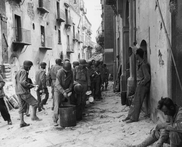 American GIs line up in the street in Troina, Sicily, utensils and dishes in hand, as they wait for a meal from a large pot, July 1943. Oregano grows abundantly in southern Italy, where many GIs encountered the herb for the first time, and fell in love.