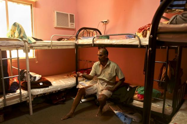 In this photo taken May 3 during a government-organized media tour, Kuttamon Chembadnan Velayi from Kerala, India, speaks to journalists while sitting on his bed in a room he shares with seven other Indian laborers in Doha, Qatar. The housing facility ha
