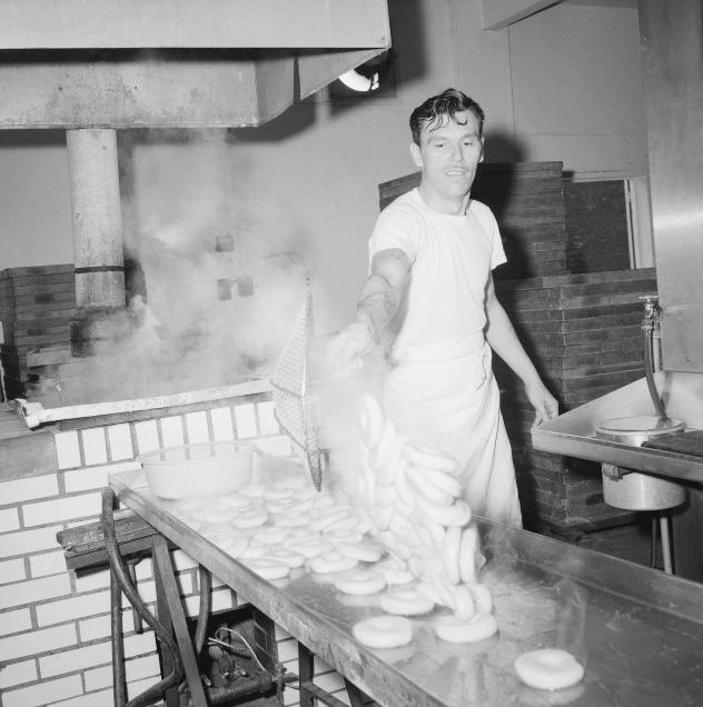Steaming-hot bagels are scooped out of the water in which they were boiled and dumped onto a stainless steel drain board at a bagel bakery in Queens, New York City, 1963. Traditionally, bagels were boiled, but bakers who use the modern method skip this s