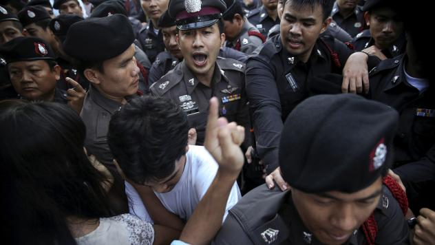 Policemen face protesters during a protest in central Bangkok on Friday. Thai authorities detained dozens of activists protesting against military rule on the first anniversary of a coup against the elected government.