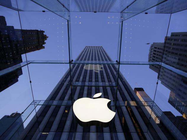 The Apple logo hangs in the glass box entrance to the company's Fifth Avenue store in New York. The company has just promoted designer Jony Ive to chief design officer.