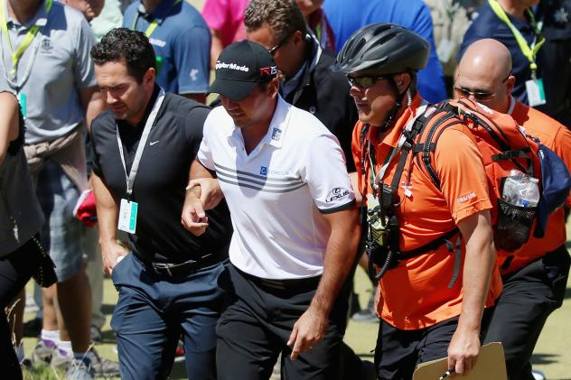 Jason Day of Australia is tended to by medical staff Friday after finishing the ninth hole during the second round of the 115th U.S. Open Championship at Chambers Bay in University Place, Wash.