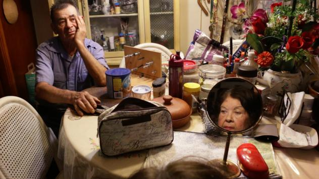 Arturo Martinez watches his wife, Aurora Martinez, put on makeup in their San Rafael, Calif., home. She has Alzheimer's.